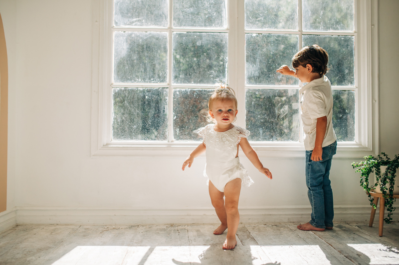 Temecula Family Photographer, little brother and sister playing near a window