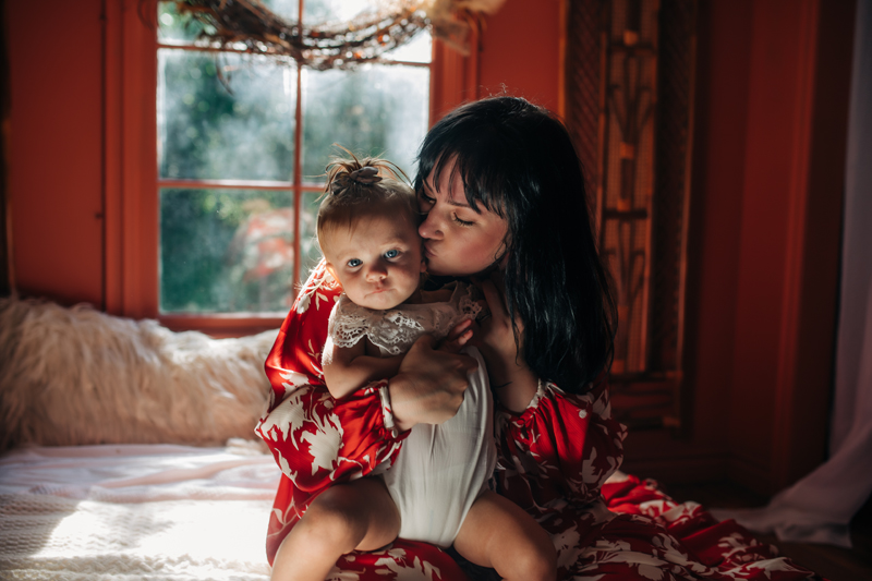 Temecula Family Photographer, mother sitting on bed kissing baby's cheek
