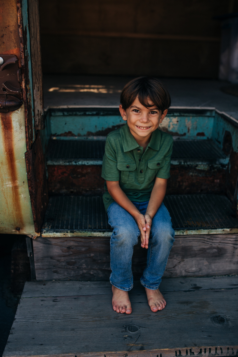 Temecula Family Photographer, little boy sitting on bus stairs