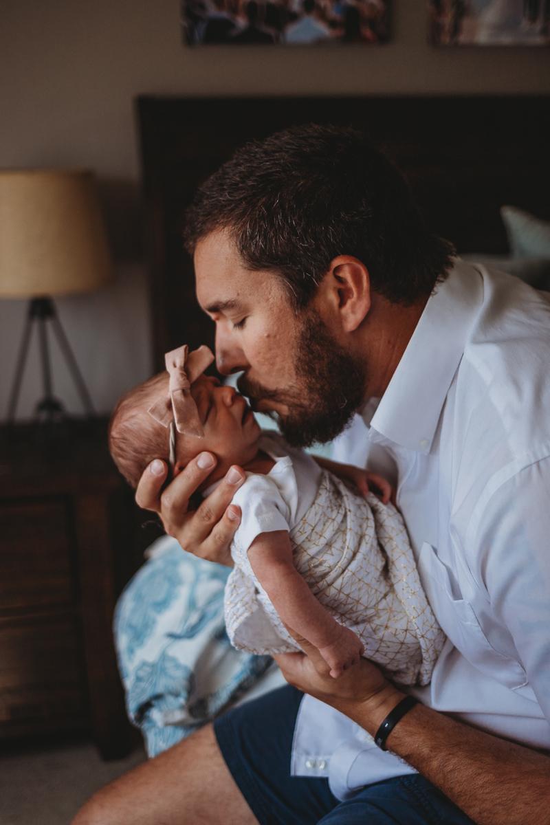 Temecula Newborn Photographer, side shot of father kissing newborn's face