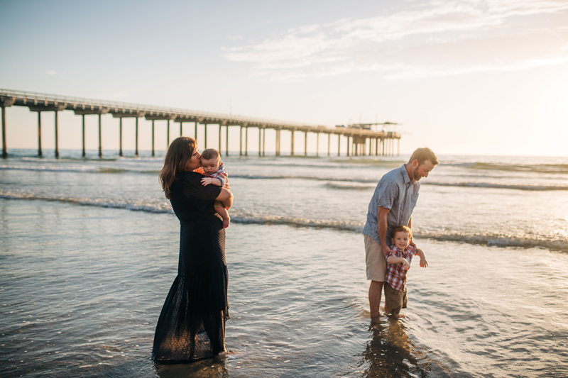 Temecula Family Photographer, mother and father playing with two little kids at the beach
