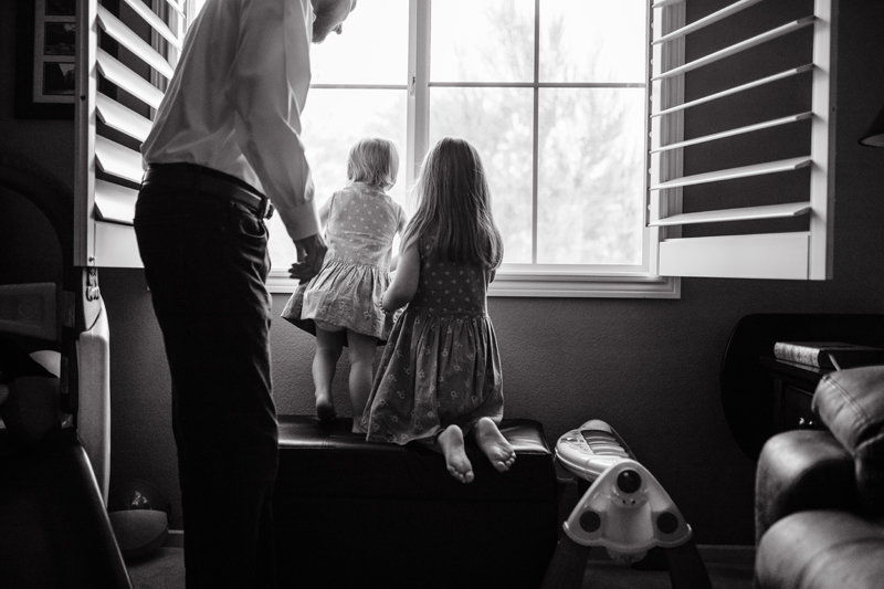 Temecula Lifestyle Documentary Photographer, father looking out the window with his two young daughters