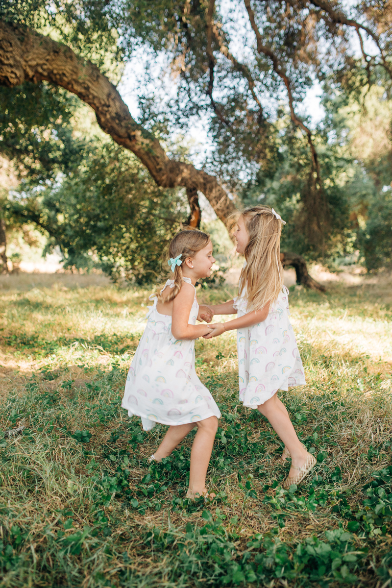Temecula Family Photographer, little sisters dancing together under a tree