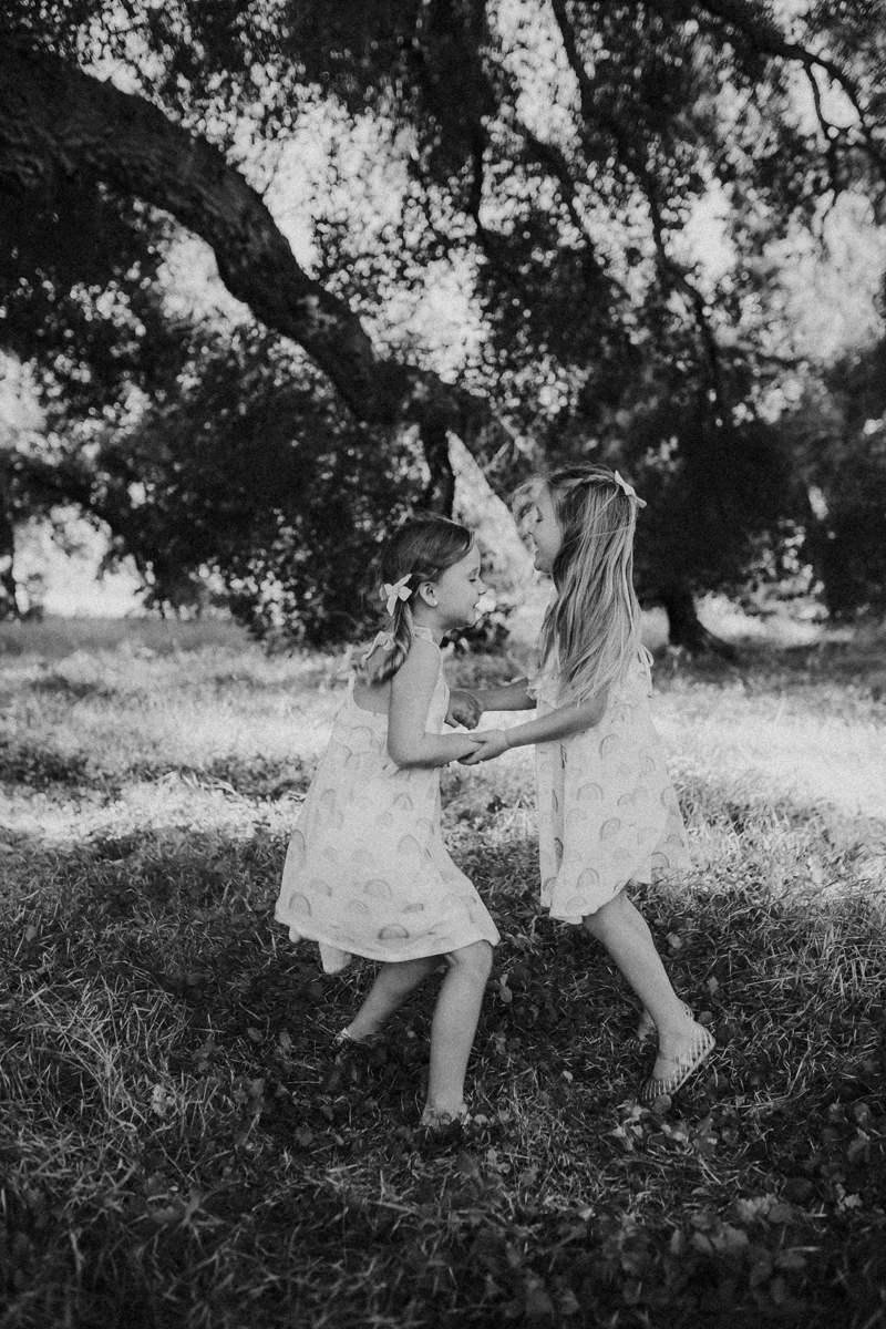Temecula Family Photographer, black and white image of little sisters dancing together